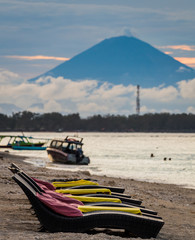 Empty beach loungers on the sand with a volcano and fishing boats in the background