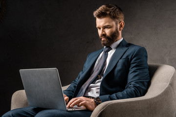 successful businessman sitting in armchair and typing on laptop