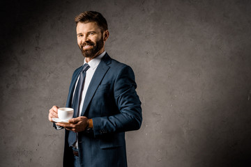 smiling businessman standing with cup of coffee