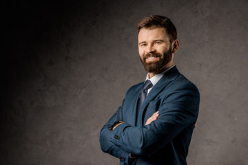 smiling bearded businessman standing with crossed arms