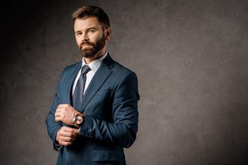 successful bearded businessman standing in formalwear