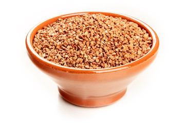A photo of raw buckwheat in an earthenware bowl on a white background with a place for text