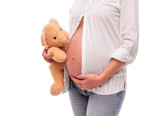 Pregnant woman is holding a bear near the belly.
