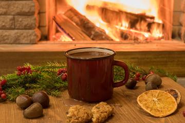 Cozy scene near fireplace with red enameled mug of hot chocolate ,mulled orange fruit, cake and nuts .