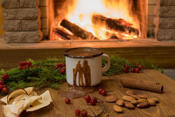 Red enameled mug with hot chocolate and christmas decorations before fireplace.