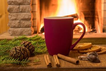 Cozy scene near fireplace with mug of hot drink , tangarine, cones and cinnamon sricks .