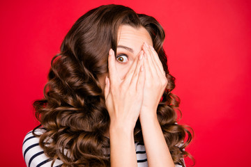 Close up portrait of closing full of fear face attractive looking she her girl watching movie horror only with one eye white striped pullover isolated on red vivid background