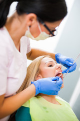 Young woman at dentist. Dentist is examining her teeth.