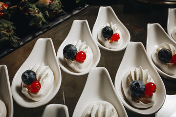 meringue with blueberries and currants on white plates wedding catering