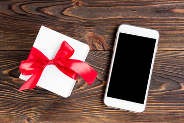 Mobile phone and gift box with red bow on wooden background.