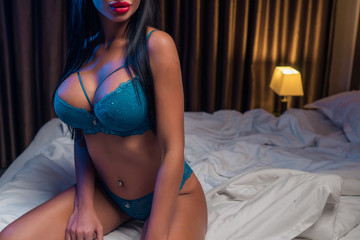 Female figure. Portrait of a girl with big breasts in sexy lingerie on the bed close-up
