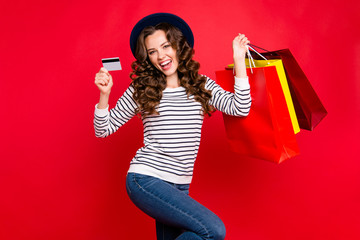 Portrait of nice adorable attractive pretty cheerful wavy-haired lady wearing striped pullover jeans denim holding in hands bags showing plastic card isolated over bright vivid shine red background