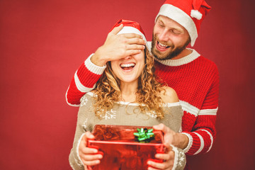 Happy boyfriend covering surprised girlfriend eyes while she's opening christmas present