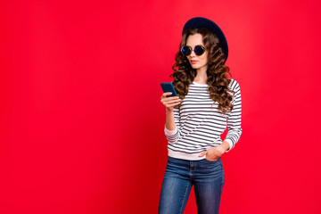 Portrait of nice lovely confident attractive slim gorgeous wavy-haired lady in striped pullover eyeglasses eyewear sunhat reading sms isolated over bright vivid shine red background
