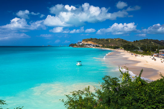 Tropical beach at Antigua island in Caribbean with white sand, turquoise ocean water and blue sky