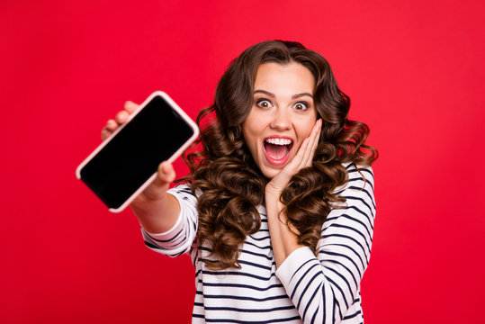 Close-up portrait of nice crazy funny attractive amazed stunned wavy-haired lady wearing striped pullover showing black screen display gadget device isolated over bright vivid shine red background
