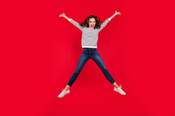 Full length size body photo of jumping high charming she her girl legs and hands apart in shape figure of star glad to win wearing white striped casual sweater on red vivid bright background