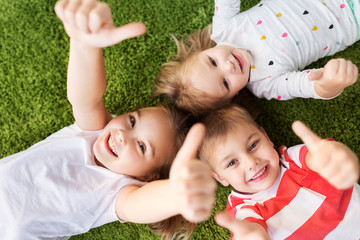childhood, leisure and family concept - happy little kids lying on floor or carpet and showing thumbs up