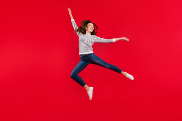 Full length size body photo of fly high attractive beautiful her girl wondering if she makes right movement wearing striped white casual sweater on red vivid bright background