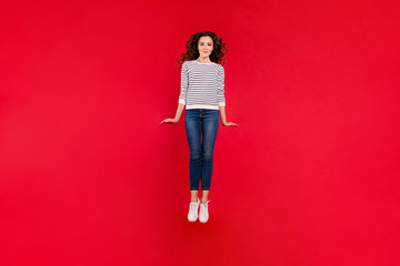 Full length size body photo of attractive she her girl with amazing wave hair jump in air wearing white casual sweater denim jeans isolated on red vivid bright background