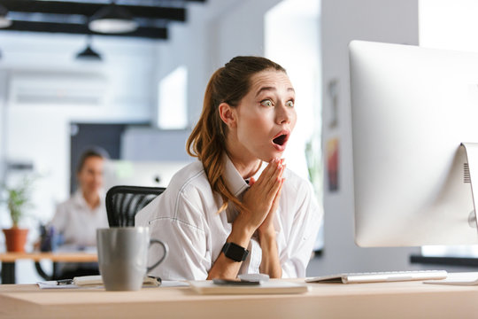 Shocked young businesswoman sitting at her workplace
