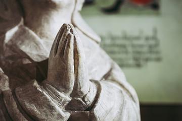 Close up sur des mains en prière, statuette religieuse