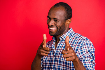 Portrait of nice handsome attractive cheerful positive guy wearing checked shirt pointing at you two forefingers inviting to party isolated over bright vivid shine red background