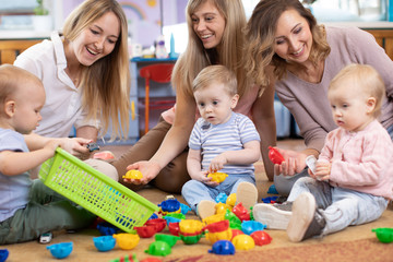 Three woman friends with babies toddlers playing on the floor in sitting room