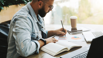 Bearded hipster man sits at table,working on laptop, and makes notes in chart, graph, diagram.Businessman analyzes data.