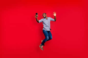 Full length body size of nice funny crazy handsome cheerful optimistic guy wearing checkered shirt holding in hands cell waving hi hello isolated on bright vivid shine red background
