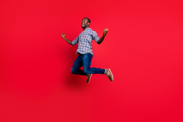 Full length body size portrait of nice funny handsome cheerful positive guy wearing checkered shirt showing winning gesture party in air isolated on bright vivid shine red background