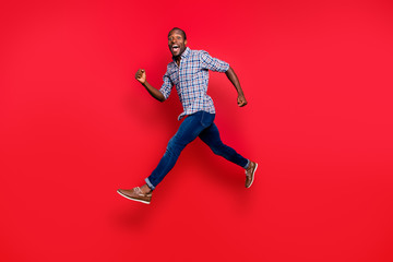 Full length body size profile side view of nice funny handsome cheerful positive sportive guy wearing checkered shirt running in air isolated on bright vivid shine red background