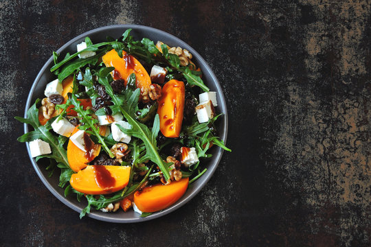 Colorful healthy persimmon salad. Vegetarian salad with persimmon, arugula and white cheese.Colorful, healthy foods in flatlay.