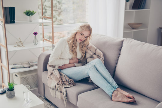 Attractive slim stylish gloomy wavy-haired lady housewife in sweater sitting on divan bare foot writhing in pain early term pregnancy digestion problem trouble disease in light white interior room