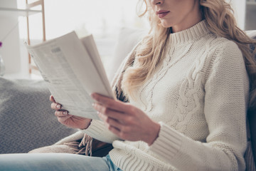 Cropped profile side view portrait of nice lovely attractive wavy-haired lady housewife wearing sweater holding in hands reading digest in light interior room