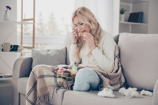 Portrait of nice lovely attractive gloomy wavy-haired lady in lotus pose crying eating large plate of tempting seductive homemade domestic baked sweets in light interior room