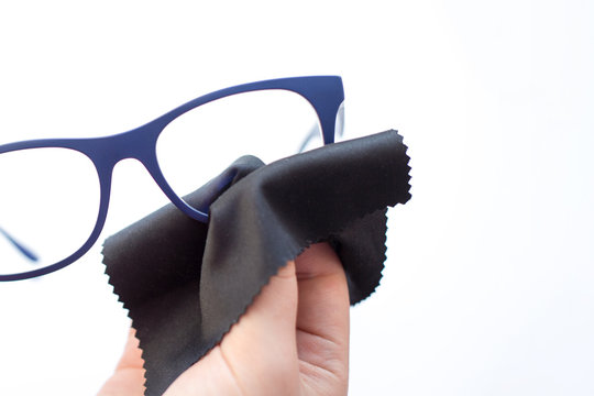 female hands wiping spectacles with a microfiber fabric