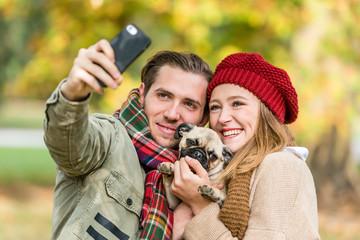 Frau und Mann mit Hund beim Herbst Spaziergang nehmen ein Selfie mit dem Handy auf