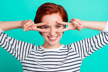 Portrait of her she nice charming attractive cheerful glad red-haired lady in striped pullover showing double v-sign on eyes isolated over bright vivid shine green turquoise background