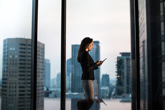 Businesswoman working late with city skyline in background