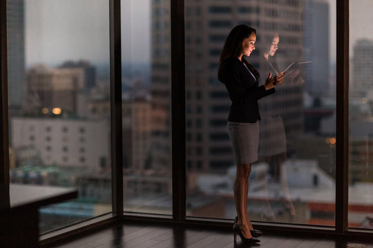 Businesswoman working late using digital tablet with city skyline in background