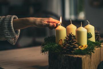 Fototapeta lighting a candle on advent wreath obraz