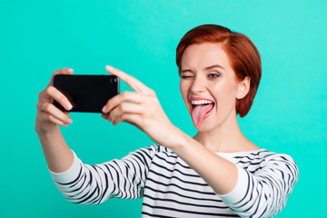 Close up portrait of cheerful attractive she her lady with telephone in hand take self photos tongue out of mouth make new post for instagram wearing white striped sweater isolated on teal background