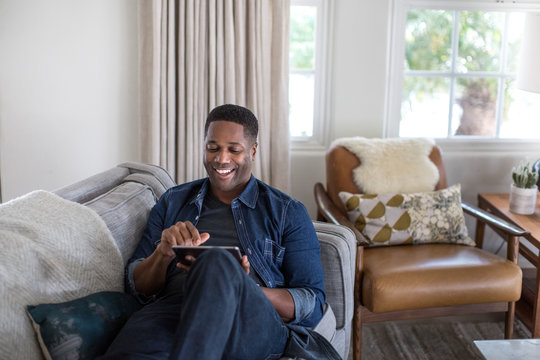 African American adult male using digital tablet at home on sofa