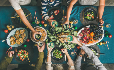 Company of friends gathering for Christmas or New Year party dinner at festive table. Flat-lay of human hands holding glasses with drinks, feasting and celebrating holiday together, top view
