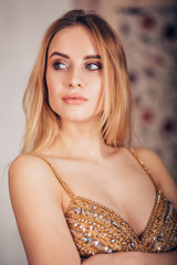 Close-up of glamorous portrait of sexy blonde woman in Golden dress. Beautiful girl looking to the side