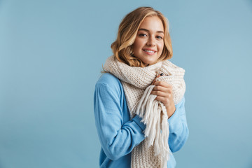 Obraz Image of blond woman 20s wrapped in scarf smiling at camera, isolated over blue background - fototapety do salonu