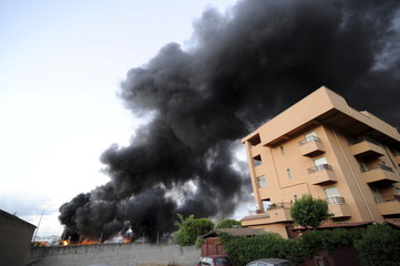 Smoke rises from a fuel depot where a fire broke out, in Palermo