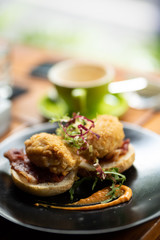 Eggs Benedict with fried breadcrumb eggs in toasted buns, with bacon and salad in a black dish.