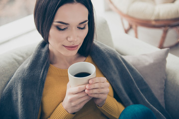 Close-up portrait of nice attractive lovely sweet tender winsome straight-haired girl wrapped in soft veil cover blanket enjoying hot cappuccino closed eyes in light interior room